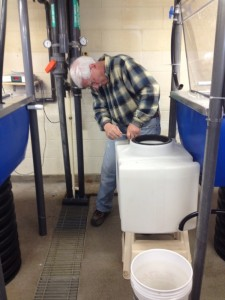 Gary Grenier (UConn Machine Shop) adjusting some fittings to the sump tanks, where gases will later be injected