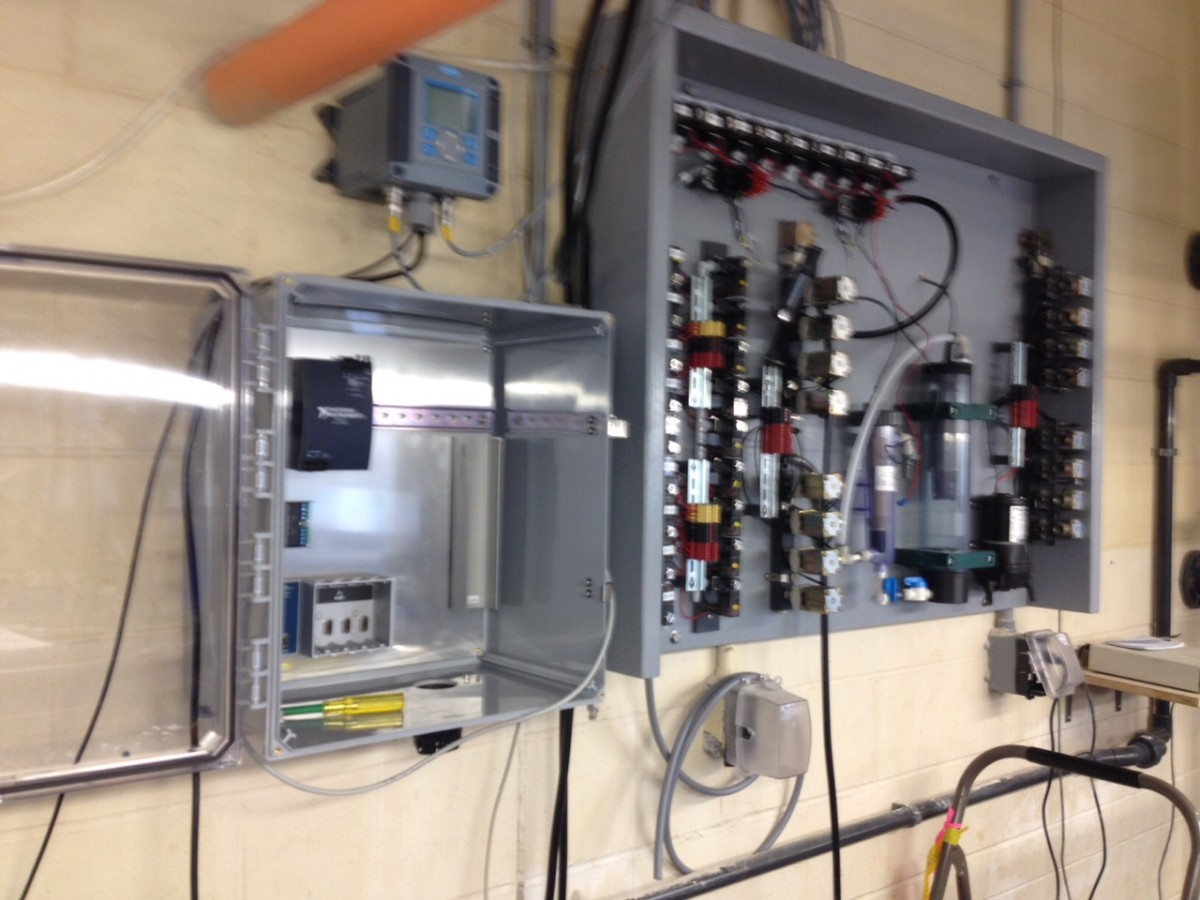 The main board of the system, not fully assembled, sporting lots of solenoid valves, flow cells, whereas the controller for pH and DO sits atop the still empty electronics box.